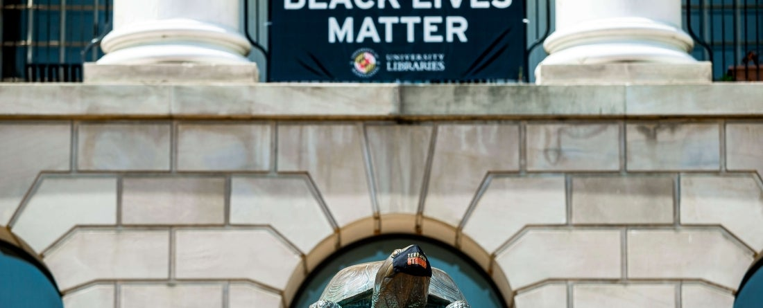 Black Lives Matter sign displayed on McKeldin Library above Testudo statue wearing face mask